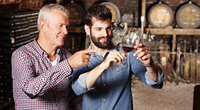 Two men, a father and adult son, look at a wine glass in a wine cellar.