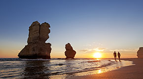 Two people walk along the beach at sunset with two of the Twelve Apostles in the background