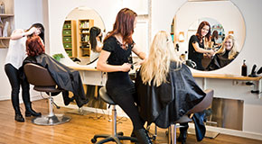 Two hairdresser cut client's hair in a well lit salon