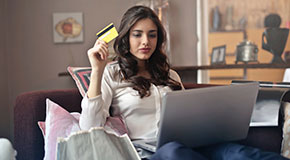 A dark haired woman sits on her couch with a laptop before her and credit card in hand.