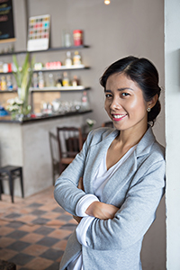female small business owner leaning on a door